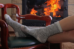 Female feet in Comfortable Warm Wool Socks. Yong woman relaxing enjoying near  fireplace. Royalty Free Stock Photos
