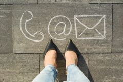 Female feet with contact symbols phone mail and letter, written on grey sidewalk, communication or contact us concept. Female feet with contact symbols phone royalty free stock photos