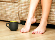 Female feet and a cup of tea or coffee Royalty Free Stock Photography