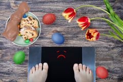 Female feet on digital scales with sad smile surrounded by Easter food Easter cake, chocolate Easter bunny, painted eggs and