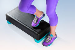Female feet do exercise on fitness aerobic stepper. Royalty Free Stock Photography