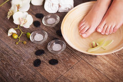 Female feet with drops of water, spa bowls, towels, flowers and candles. Female feet with drops of water, spa bowls, towels, flowers and candles Royalty Free Stock Images