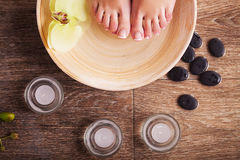 Female feet with drops of water, spa bowls, towels, flowers and candles. Royalty Free Stock Images