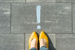 Female feet with exclamation point, symbol of attention drawn on the asphalt Royalty Free Stock Photos