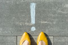 Female feet with exclamation point, symbol of attention drawn on the asphalt.  stock photos