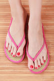 Female feet with flip-flops. On wooden floor Stock Photo