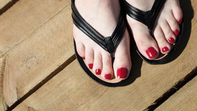 Female feet with flip-flops red nail Stock Photography