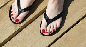 Female feet with flip-flops red nail Royalty Free Stock Images