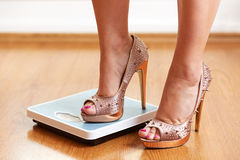 Female feet in golden stilettos with weight scale Royalty Free Stock Images