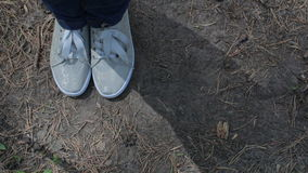 Female feet in gray sneakers gumshoes moving on a ground stock video