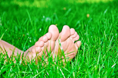 Female feet in green grass. Close-up Royalty Free Stock Photos