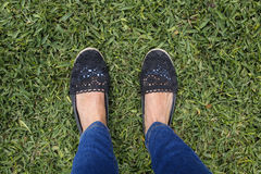 Female feet on green grass. Suntanned female feet on green grass Royalty Free Stock Photography