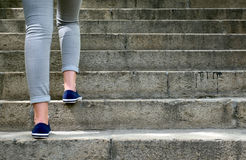 Female feet in gym shoes to climb the stairs Stock Photos