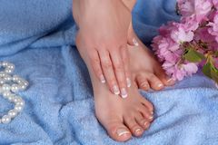 Female feet and hands with french manicure and pedicure in spa salon on blue blue towel with decorative flower and pearls stock image