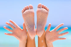 Female feet and hands on sea background. Female feet and hands on blue sky and sea background Royalty Free Stock Images