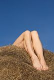 Female feet on hay, against darkly blue sky Royalty Free Stock Photography