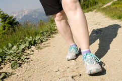Female feet are hiking in the mountains Stock Photos