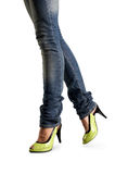 Female feet in jeans. And in green shoes Stock Images