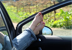 Female feet in jeans rolled up resting on opened car door. Female feet in jeans rolled up resting placed on opened car door outdoor in rural place in sunny Royalty Free Stock Photos