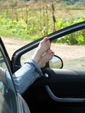 Female feet in jeans rolled up resting on opened car door. Female feet in jeans rolled up resting placed on opened car door outdoor in rural place in sunny Stock Photography