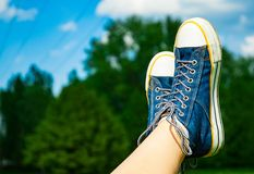 Female feet in jeans sneakers on the background of a sky and tree. Sunny summer day Royalty Free Stock Images