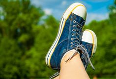 Female feet in jeans sneakers on the background of a sky and tree. Sunny summer day Stock Image
