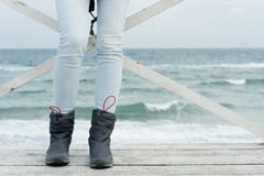 Female feet in jeans and sports boots on wooden boards against the sea. Close-up Stock Images