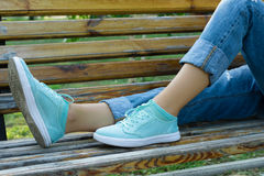 Female feet in jeans and sports shoes on a bench close-up. Girl resting on a bench after a walk in the park Stock Image