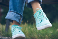 Female feet in jeans and sports shoes in the park close up. Woman sitting on a bench near the green grass. Rest after walking Royalty Free Stock Image