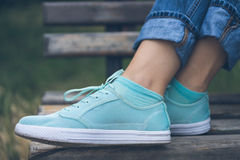 Female feet in jeans and sports shoes Royalty Free Stock Image