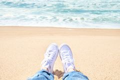 Female feet in jeans and white sneakers on beach. Walk along the beach. In summer day Royalty Free Stock Image