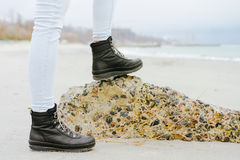 Female feet in jeans and winter boots standing on a stone on the. Coast Royalty Free Stock Photos