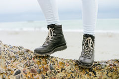 Female feet in jeans and winter boots standing on a stone on the. Coast close-up Stock Image