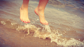 Female feet jump on beach. Happiness and craziness. Female legs feet in air jump on beach over water. Fun and freedom Stock Photos