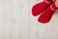 Female feet in knitted red socks on white wooden background. Stock Photos