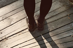 Female feet in lacquered shoes on wooden background Royalty Free Stock Image