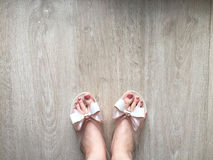 Female Feet and Legs with Pedicure in Pink Slippers on a Wooden Floor Royalty Free Stock Photography