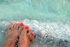 Female feet with manicure on stone, covered with salt formations between the waves in the water. Crystallization of salt on stone stock photo