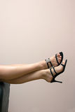 Female feet over couch in sandals Royalty Free Stock Photo