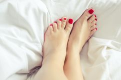 Female feet with a pedicure. Well groomed bare feet on white bedding, close up. Skin care. Woman body legs bed awaking morning step sleep relax concept stock photos