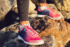Female feet in pink and blue sneakers standing on the rocky stone Royalty Free Stock Photography