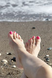 Female feet with pink nail polish by the sea. Beautiful woman feet with pedicured toes laying on the mediterranean beach royalty free stock photography