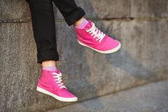 Female feet in pink sneakers. On stone wall Stock Photography