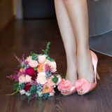 Female feet in pink wedding sandals with a wedding bouquet Stock Photos