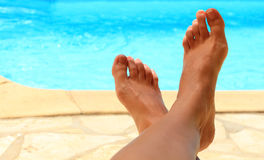 Female feet by the poolside. Blue waters Stock Images