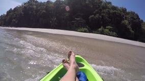 Female feet pov on boat kayak approaching the shore, wild uninhabited, wild adventure water activity, leisure sport.  stock video