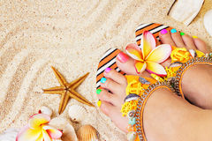 Female feet with pretty multicolor pedicure on sand, with frangipani flowers and seashells. Summertime concept royalty free stock image
