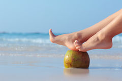 Female feet propped on coconut on sea background. Female feet propped on coconut on the beach, blue sea background royalty free stock photos