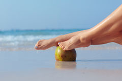 Female feet propped on coconut on sea background royalty free stock photography