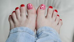 Female feet with red lacquer on nails on couch stock footage